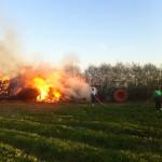 Mit Hilfe eines Traktors werden die brennenden Strohballen auseinander gezogen.